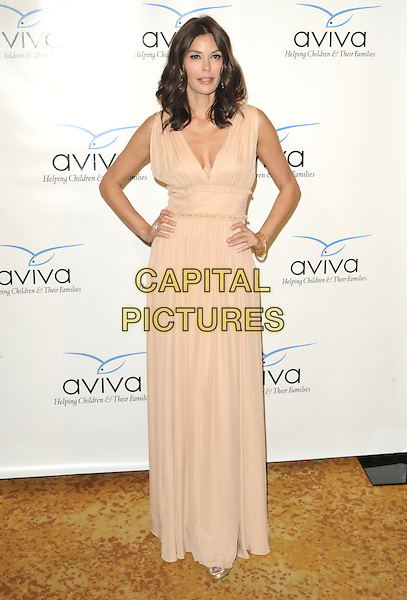 TERI HATCHER .at the Aviva Family & Children's Services 2010 The A Gala at The Beverly Wilshire Four Seasons Hotel in Beverly Hills, California, USA, April 17th 2010..full length beige nude sleeveless Grecian long maxi dress hands on hips                                                                   .CAP/RKE/DVS.©DVS/RockinExposures/Capital Pictures.