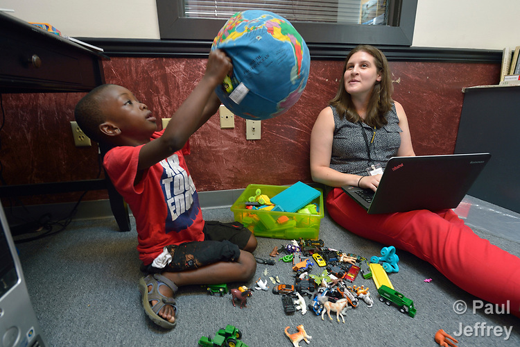 Christine Baer, a congregational resource developer with Church World Service, sits on the floor of her office in Lancaster, Pennsylvania, accompanied by David Kalamba, a 6-year old resettled refugee from the Democratic Republic of the Congo. Church World Service resettles refugees in Pennsylvania and other locations in the United States. <br /> <br /> Photo by Paul Jeffrey for Church World Service.