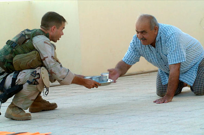 A U.S. Sniper receives refreshments from an Iraqi home owner on his rooftop where the sniper team watched for insurgent activities on the streets of Mosul, Iraq. Wednesday July 6, 2005.