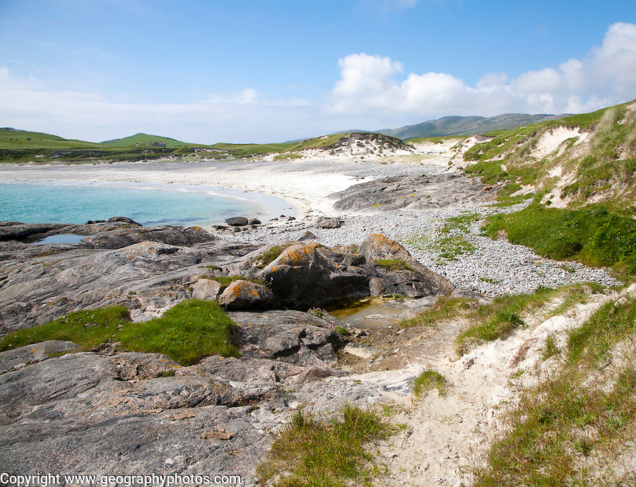 Rocky headland and sandy beach at Bagh a Deas, South Bay, Vatersay island, Barra, Outer Hebrides, Scotland, UK