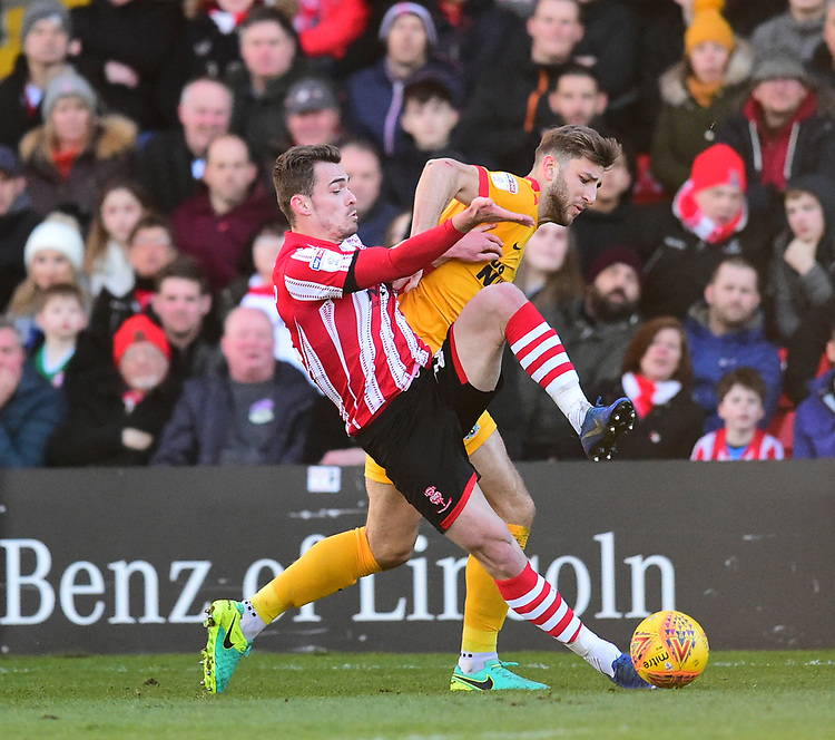 Lincoln City's Harry Toffolo vies for possession with  Northampton Town's Charlie Goode<br /> <br /> Photographer Andrew Vaughan/CameraSport<br /> <br /> The EFL Sky Bet League Two - Lincoln City v Northampton Town - Saturday 9th February 2019 - Sincil Bank - Lincoln<br /> <br /> World Copyright © 2019 CameraSport. All rights reserved. 43 Linden Ave. Countesthorpe. Leicester. England. LE8 5PG - Tel: +44 (0) 116 277 4147 - admin@camerasport.com - www.camerasport.com