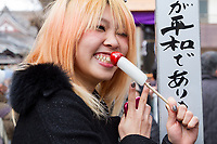 A Japanese woman eats a penis shaped lollipop at the Kanamara matsuri or festival of the Steel phallus Kawasaki Daishi, Kawasaki, Kanagawa, Japan. Sunday, April 2nd 2017. The Kanamara Penis festival takes place on the first Sunday of April and celebrates the local legend of a penis eating demon who was defeated after being tricked into biting a steel phallus. The festival is popular with Japan's gay community and now uses its notoriety to raise money for HIV and AIDS charities. It is also wildly popular with foreign and Japanese.tourists.