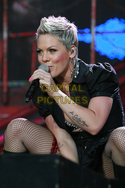 PINK (Alecia Beth Moore).Performing live at Wireless Festival in Hyde Park, London, England, UK, .July 3rd 2010..piink pinnk concert music gig live on stage half length  black ruffle dress bra bikini top shirt hoop earrings silver microphone red garter fishnet tights tattoo on thigh arm bending singing .CAP/MAR.© Martin Harris/Capital Pictures.