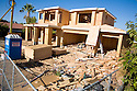 A large two-story conventional wood frame house is under construction. Large amounts of wood and other raw materials are being used to build this new house on a lot where a small single-story home was demolished. Cupertino, California, USA