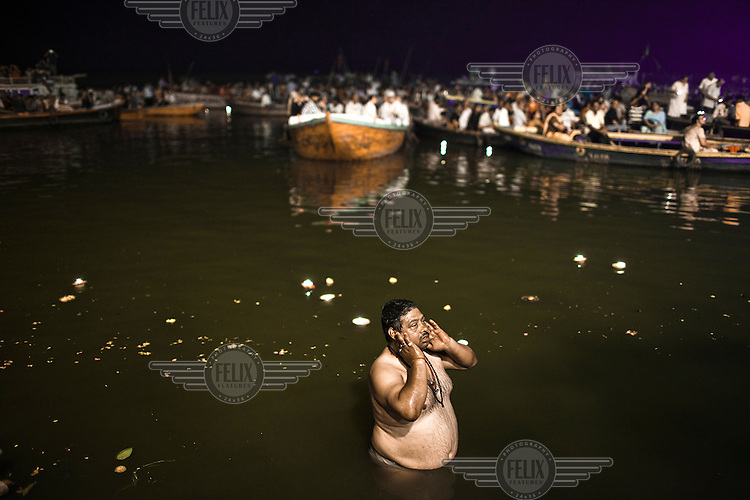 A pilgrim looks on after taking a holy dip in the Ganges River at the Dashashwamedh Ghat in the ancient city of Varanasi.