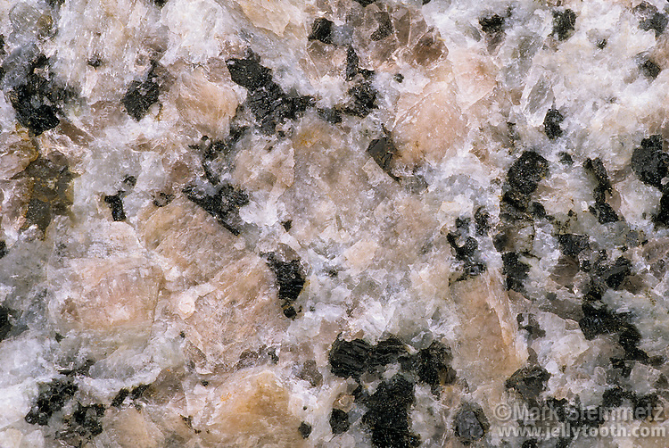 Close-up of granite, showing its coarse-grained structure. Granites vary in composition, but always consist of the minerals feldspar and quartz, and usually mica and hornblende. 1x magnification at 35mm.