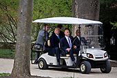 U.S. President Donald Trump, center, sits in a golf cart while touring outside the Mansion at the Mount Vernon estate of first U.S. President George Washington in Mount Vernon, Virginia, U.S., on Monday, April 23, 2018. As Macron arrives for the first state visit of Trump's presidency, the U.S. leader is threatening to upend the global trading system with tariffs on China, maybe Europe too. <br /> Credit: Andrew Harrer / Pool via CNP