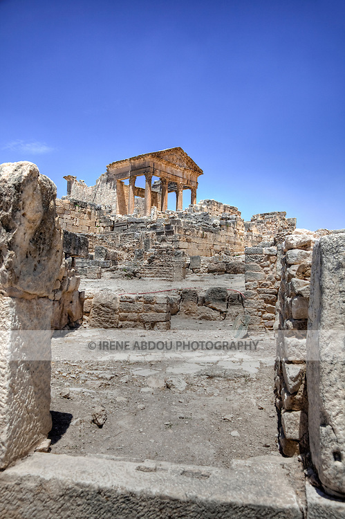Named as a UNESCO World Heritage Site in 1997 and located southeast of Tunis, the Roman ruins of Dougga are renowned as the largest and most beautiful Roman site in all of Tunisia.  This photo shows the well-preserved temple of the Capitol in the distance.