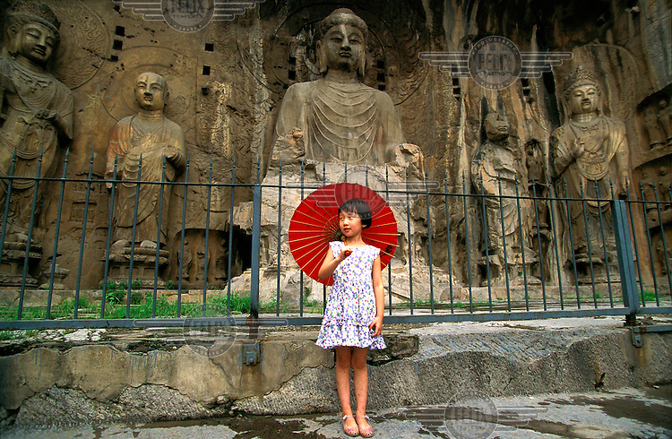 ©Mark Henley/Panos Pictures..China, Henan, Luoyang..Longmen Buddhist Caves. Ancestor Worshipping Temple. Girl posing with parasol with Buddha behind.