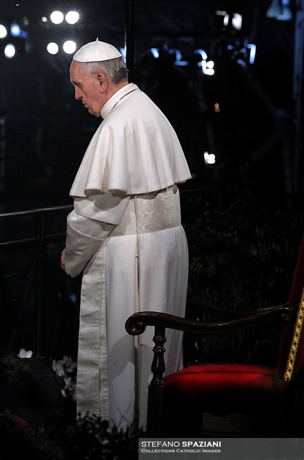 Pope Francis holds the wooden cross during the Via Crucis (Way of the Cross) torchlight procession on Good Friday in front of the Colosseum in Rome.March 29, 2013