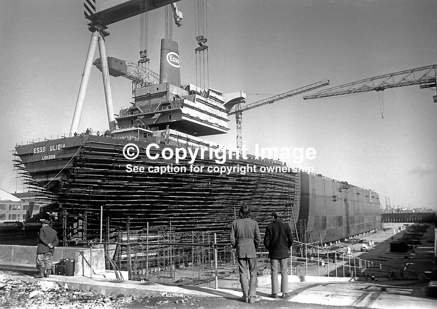 Esso Ulidia under construction at the Belfast, N Ireland shipyard of Harland &amp; Wolff. The giant crane &quot;Goliath&quot; is manoevering the upper decks superstructure into place. 5th March 1970. It went to the breakers yard in 1983. 197003050095c<br />