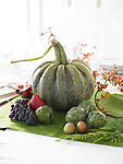 An decorative centerpiece with green pumpkin, grapes, artichokes, pears, and pomegranate