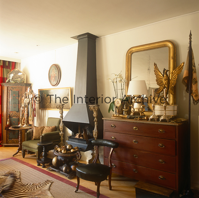 A sitting room with a fireplace with a steel chimney. A gilt mirror and other gilded objects are arranged on an antique chest of drawers.