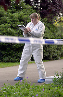 Scenes of crime officer in a white suit dusting for fingerprints after an incident took place in a park. Two men were fighting over a can of beer and one stabbed the other and ran off. The officer is making detailed notes. The area has been cordoned off with police barrier tape...© SHOUT. THIS PICTURE MUST ONLY BE USED TO ILLUSTRATE THE EMERGENCY SERVICES IN A POSITIVE MANNER. CONTACT JOHN CALLAN. Exact date unknown.john@shoutpictures.com.www.shoutpictures.com..