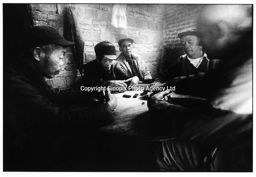 Old men sit around playing mahjong in a village in Huaji County, Guangdong Province, China. The village is largely devoid of men and young women who have left the village for work in the cities. The farmers live a frugal existence below the poverty line. The poverty gap in China is a major theme at this years National People's Congress in Beijing since it is causing destabilisation of the country....PHOTO BY SINOPIX
