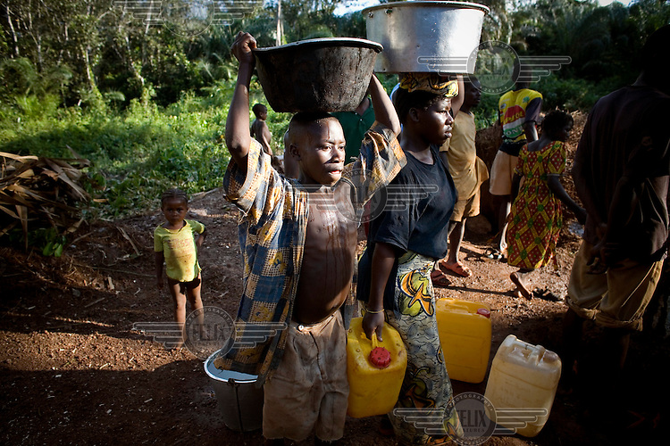 A girl and a boy carry water from a well in buckets and plastic bottles.