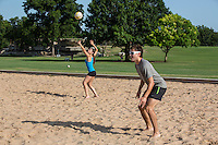 Group of friends playing volleyball on the Zilker Park sand volleyball courts, female returning the serve ball in play during summer volleyball tournament play in Austin, Texas.