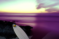 A surfboard leans on black coral against a purple tinted ocean at sunset on the north shore of Oahu.