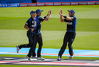 Tim Southee (right) congratulates Adam Milne for catching Eoin Morgan during the ICC Cricket World Cup one day pool match between the New Zealand Black Caps and England at Wellington Regional Stadium, Wellington, New Zealand on Friday, 20 February 2015. Photo: Dave Lintott / lintottphoto.co.nz