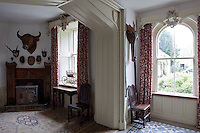 Floral curtains hang from ornately carved pelmets in the entrance hall which is decorated with hunting trophies