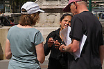 """France, Paris.  Street Photography.<br /> I must look like a tourist. I was approached by this """"gold ring"""" scam so often, the next time I was ready to take a photo. Fortunately, someone more savvy than these tourists, stopped and suggested this young woman is not to be trusted. The streets of Paris."""