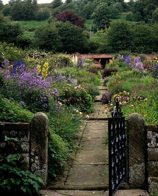 A small wrought-iron gate opens onto a floral garden rising up to a summer house