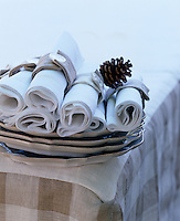 Hand-made napkin rings fastened with a button and decorated with a pine cone