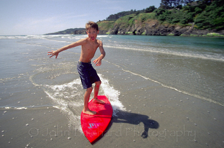 Young boy skim boarding at Big River, Mendocino California