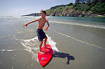 Young boy skim boarding at Big River, Mendocino California