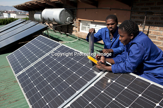 CAPE TOWN, SOUTH AFRICA - APRIL 20: Isaac Molelelu and Thabisa Siyokwana, installs and checks solar panels on April 20, 2012 in Cape Town, South Africa. They study at a solar installation course.The students come from poor backgrounds and have been unemployed until they cam here. iThemba Labantu offers these young men and women the opportunity to learn a trade so that they will be able to earn a living for themselves and their families one day. (Photo by Per-Anders Pettersson For Global Post)