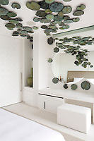 An artwork of lily pads decorates the ceiling and walls of the bedroom suite in the Villa Siam at Iniala