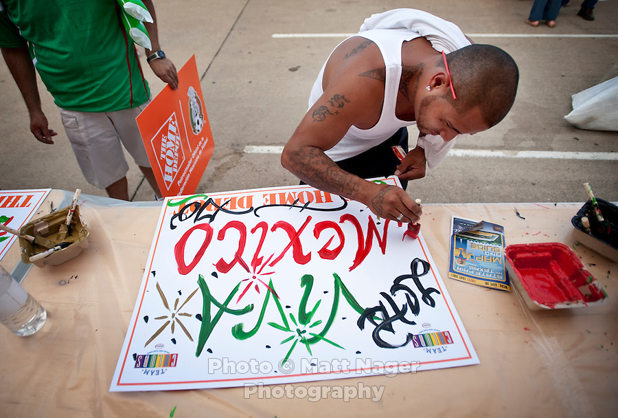 Sammy Garcia (cq) works on painting a poster reading Viva Mexico outside the Cotton Bowl before Mexico played Colombia in an exhibition game in Dallas, Texas, USA, Wednesday, Sept., 30, 2009. Colombia won the game 2-1, which was played as the second game of a double header after a FC Dallas soccer game, in an attempt by Major League Soccer to draw a new crowd of hispanic people to the sport in the US...PHOTOS/ MATT NAGER