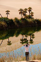 A woman stands admiring the spectacular scenery of the  Uhm al Maa lake in the Ubari desert