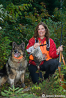Successful woman hunter and dog holding ruffed grouse