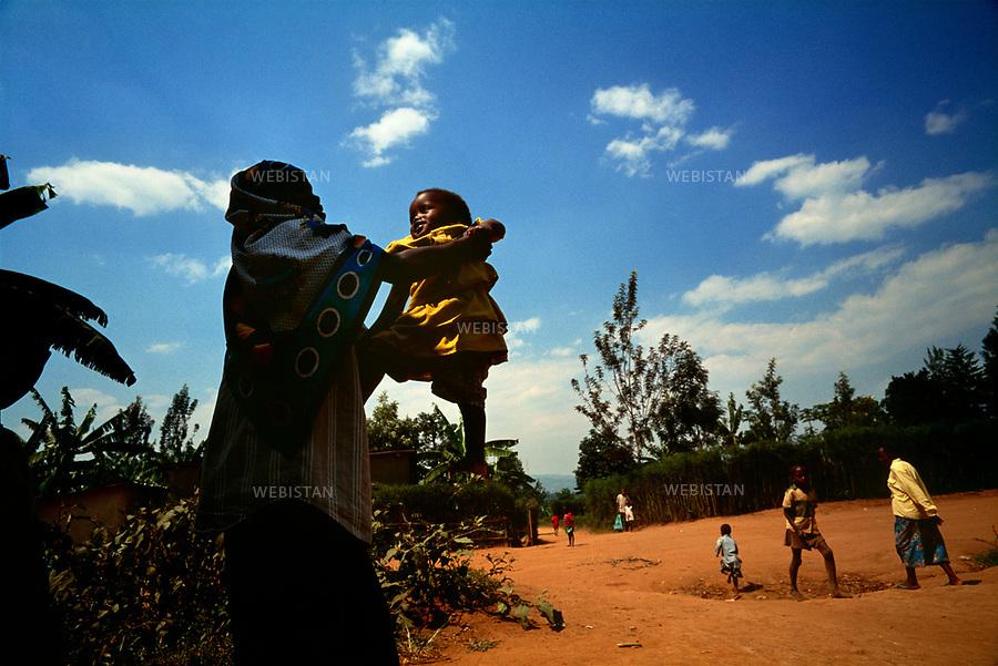1996. Rwanda. Near Kigali. Jacqueline, a Tutsi refugee woman, holds her daughter Diane, born from the rape of her mother by a Hutu during the 1994 Rwandan Genocide. Rwanda. Près de Kigali. Jacqueline, une réfugiée tutsie, porte sa fille Diane, née du viol de sa mère par un Hutu pendant le génocide au Rwanda en 1994.