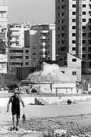 Albania. Province of Durres. Durres. New buildings and old bunker on the Mediterranean sea front. An underwater fisherman catched an octopus. Enver Hoxha (1908-1985) was for 40 years a dictator and a communist leader. He decided after the historic break with Russia in 1961 to protect his country from any invaders by investing in a massive fortification (more than a million bunkers were built over the years till 1985). © 2003 Didier Ruef