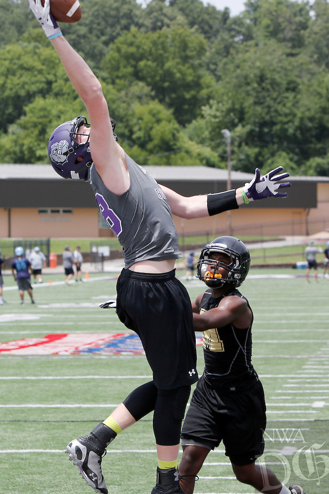 NWA Democrat-Gazette/DAVID GOTTSCHALK - Fayetteville High School's Drake Wymer catches a touchdown pass between Midwest City High School defenders Friday, July 10, 2015 during the Southwest Elite 7 on 7 tournament at Fayetteville High School.