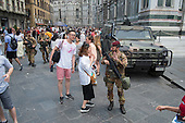 Soldier on guard amongst crowds on guided tours outside the Duomo cathedral Florence, Italy.