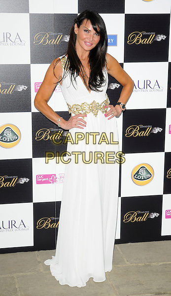 LIZZIE CUNDY .Attending The Grand Prix Ball at The Hurlingham Club, London, England, .UK, 7th July 2010. .full length dress white sleeveless gold long maxi hands on hips .CAP/CAN.©Can Nguyen/Capital Pictures.