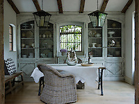 Wicker chairs and white cowhide soften the industrial edge of the table in the dining room, which extends a further three feet