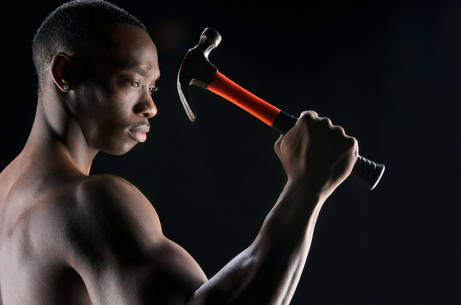 Young african american showing his muscles and ready to work with hammer.