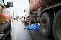 SAO PAULO, SP, 06.11.2013 -  ACIDENTE MOTO X CAMINHÃO -- COM VITIMA - Caminhão e moto se envolveram em um acidente na pista central da Marginal Tietê, na altura da Ponte do Limão sentido Rod. Ayrton Senna na tarde desta quarta feira (06). O Motociclista  veio a óbito no local, uma das pista da via central da marginal está interditada. (Foto: Marcelo Brammer / Brazil Photo Press).