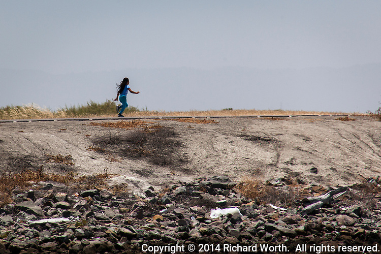 A young girl joyfully runs along the par course path at the San Leandro Marina Park.