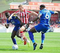 Lincoln City's Danny Rowe vies for possession with Tranmere Rovers' Zoumana Bakayogo, left, and Tranmere Rovers' Emmanuel Monthe<br /> <br /> Photographer Chris Vaughan/CameraSport<br /> <br /> The EFL Sky Bet League Two - Lincoln City v Tranmere Rovers - Monday 22nd April 2019 - Sincil Bank - Lincoln<br /> <br /> World Copyright © 2019 CameraSport. All rights reserved. 43 Linden Ave. Countesthorpe. Leicester. England. LE8 5PG - Tel: +44 (0) 116 277 4147 - admin@camerasport.com - www.camerasport.com