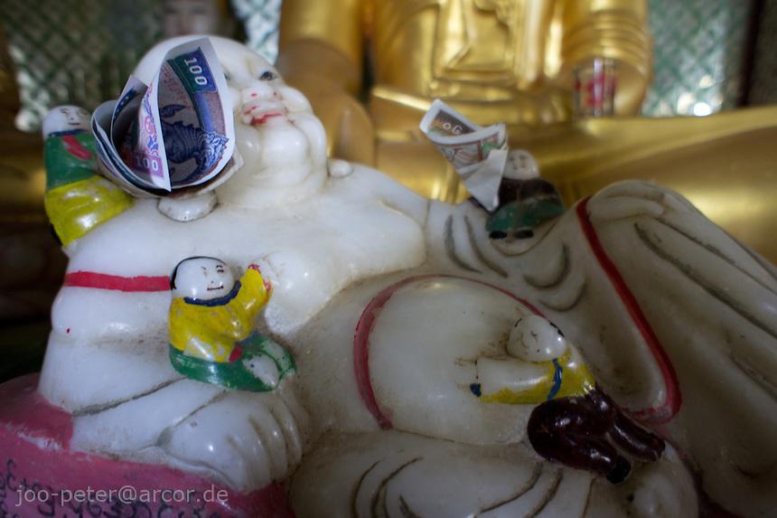 spirit happy to receive money as offering in temple of  Mount Popa, Myanmar, 2011