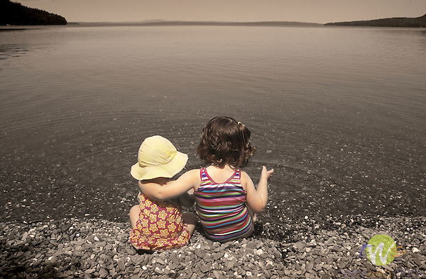 Sophie and Ellie, sisters, talking along shoreline of Moosehead Lake, Maine.