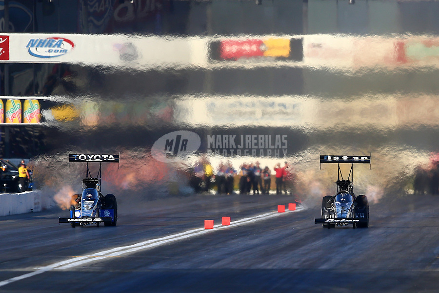 Nov 8, 2013; Pomona, CA, USA; NHRA top fuel dragster driver Antron Brown (left) races alongside Shawn Langdon during qualifying for the Auto Club Finals at Auto Club Raceway at Pomona. Mandatory Credit: Mark J. Rebilas-