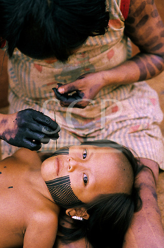 A-Ukre Village, Xingu, Brazil. Kayapo boy having an intricate design painted on his face using genipapo dye.
