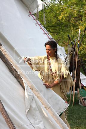 Native American Lakota Indian woman breaking down a tipi to move