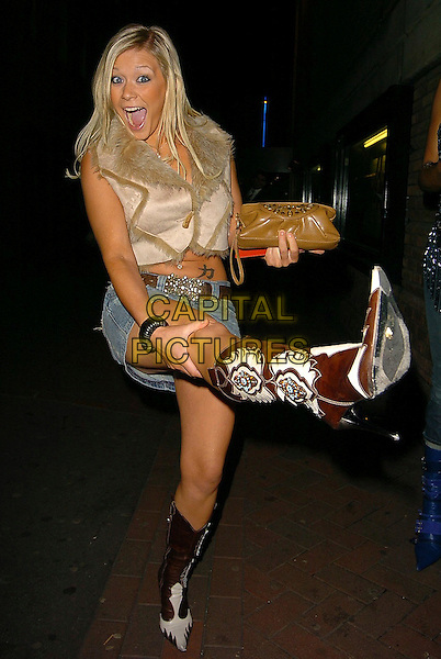 """LEANNE WILSON & GUEST.UK Premiere of """"Kinky Boots"""" at Vue West End, Leicester Square, London..October 4th, 2005.full length denim jean skirt cowboy boots tattoo fur gilet vest funny mouth open kicking gesture.www.capitalpictures.com.sales@capitalpictures.com.©Capital Pictures"""